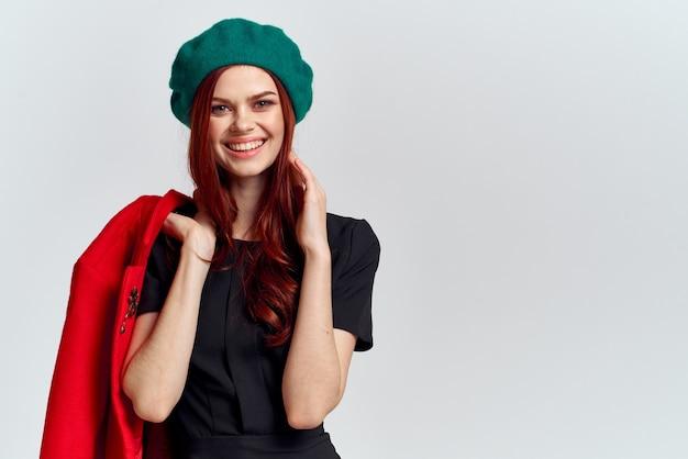 Женщина держит в руке красное пальто и темную футболку зеленая шляпа