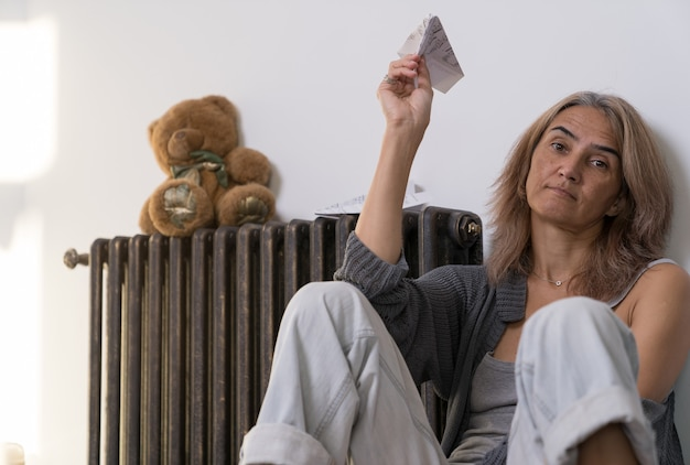 ある女性がアパートの床に音符の入った紙でできた飛行機を手に持っている