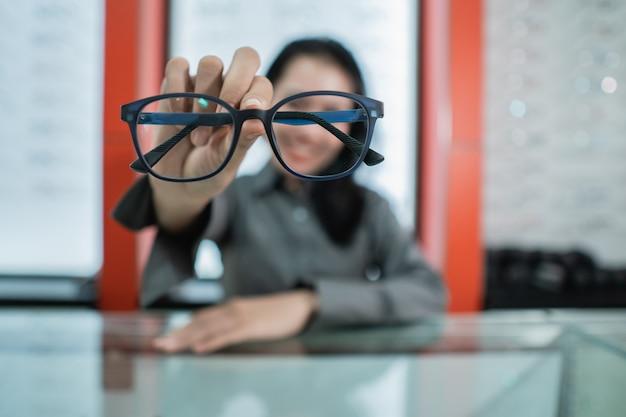 Женщина держит очки, которые она выбирает в офтальмологической клинике.