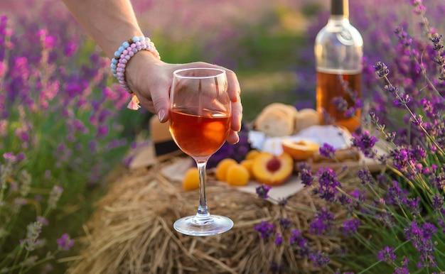女性はグラスにワインを持っています。ラベンダー畑でのピクニック。セレクティブフォーカス。自然。