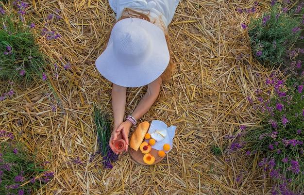Женщина держит вино в бокалах. пикник в лавандовом поле. выборочный фокус.
