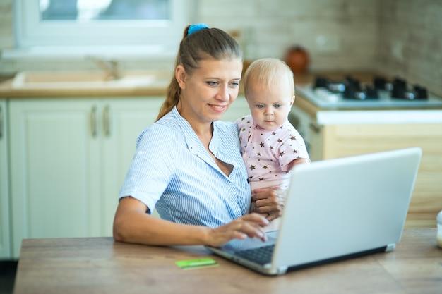 부엌에서 집에 있는 여성 주부는 노트북과 작은 아기와 함께 테이블에 앉습니다. 의사 소통, 휴식, 재택 근무 및 온라인 쇼핑