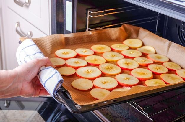 女性主婦がスライスしたりんごの天板を電気オーブンに入れて乾かします。ドライフルーツ、健康食品。水平方向、セレクティブフォーカス。