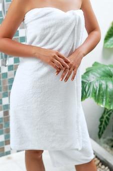 수건으로 목욕하는 여자. 미용 및 바디 케어.