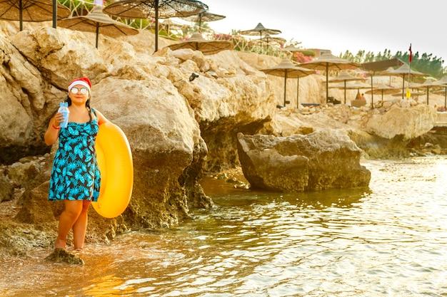 Женщина в купальном платье и шляпе санты на берегу моря у скал