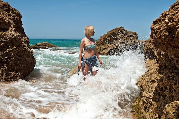 수영복을 입은 여성이 큰 파도와 함께 석호에 서 있습니다.
