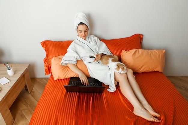 목욕 가운과 샤워 후 그녀의 머리에 수건을 가진 여자는 노트북 뒤에 고양이와 함께 침대에 누워