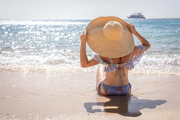 大きな帽子をかぶった女性が海のコピースペース近くのビーチで日光浴をします。