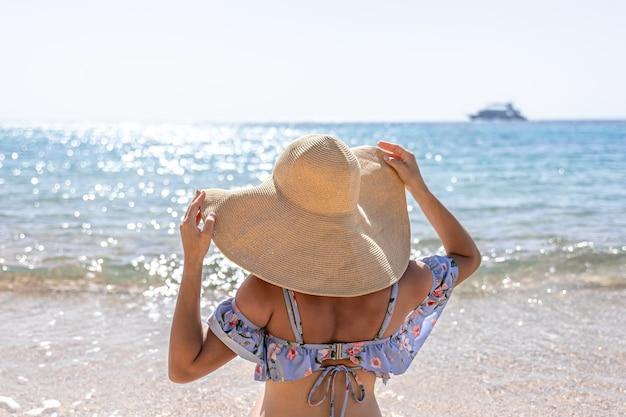 大きな帽子をかぶった女性が海の近くのビーチで日光浴をします。
