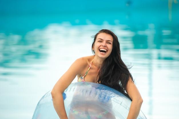 고무 풍선 원이있는 비키니 입은 여자가 여름에 놀이 공원 수영장에서 즐거운 시간을 보내고 있습니다.
