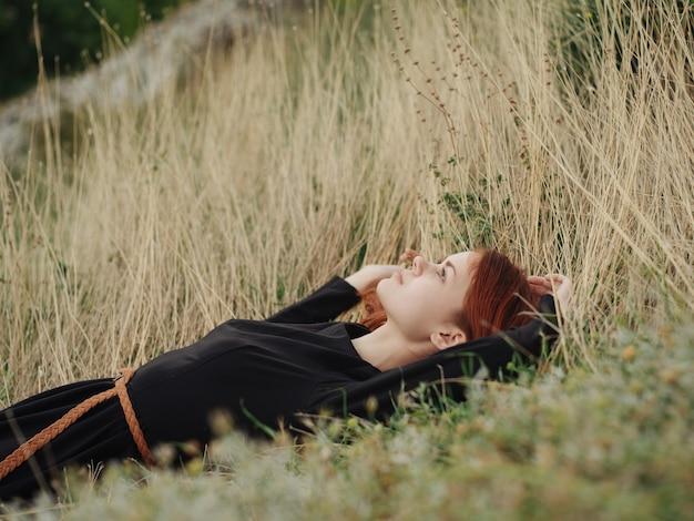 Женщина в черном платье лежит на сухой траве на лугу на природе