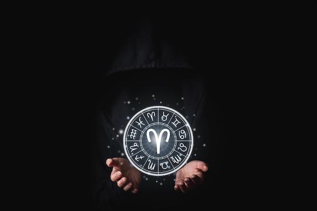 손바닥으로 검은 망토를 입은 여성이 황도대의 빛나는 점성술을 들고 있다