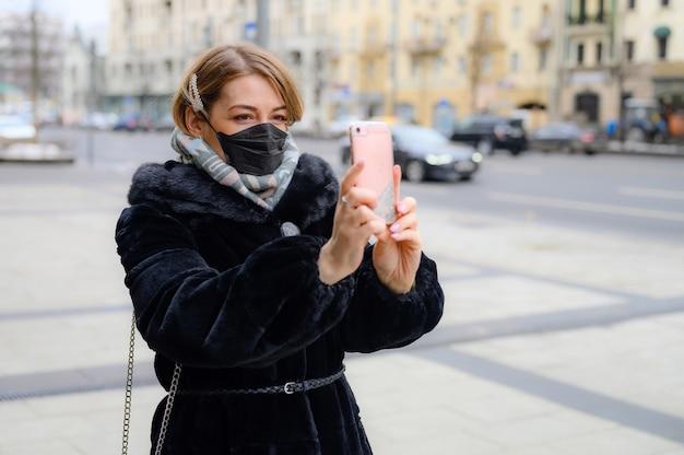 黒い医療用マスクの女性が街の屋外の冬に自分撮り写真を撮る