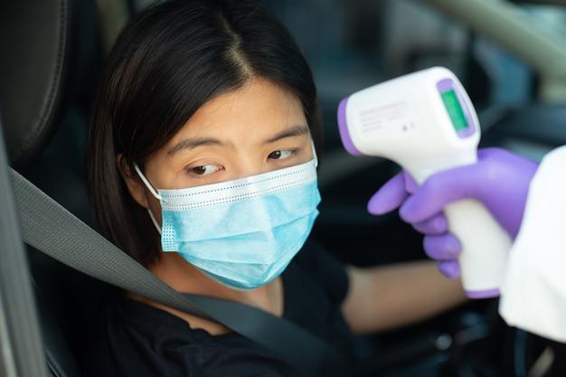 黒いシャツを着た女性が小さな体温計で測定されています。