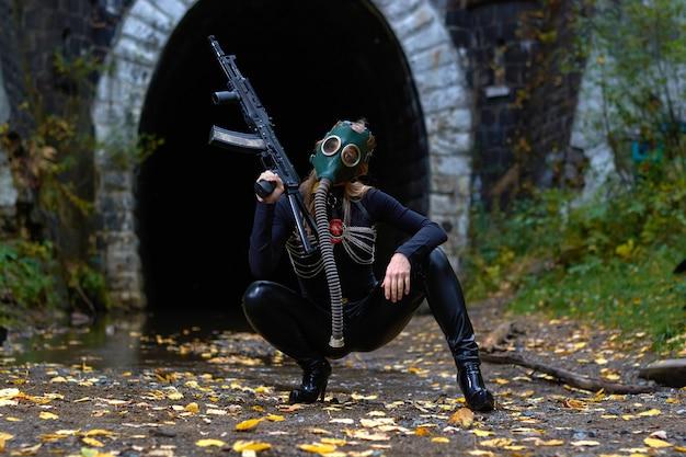 機関銃を手にした黒いスーツと防毒マスクを着た女性。