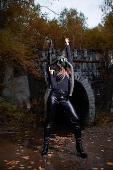 Женщина в черном костюме и противогазе с автоматом в руках.