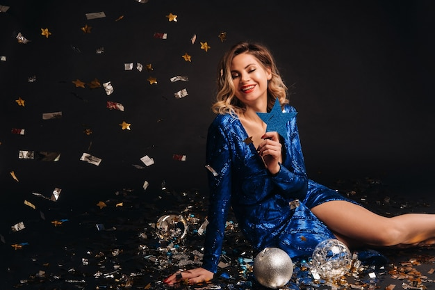 파란색 반짝이 드레스에 여자는 검정색 배경에 색종이와 바닥에 앉아 웃 고있다.