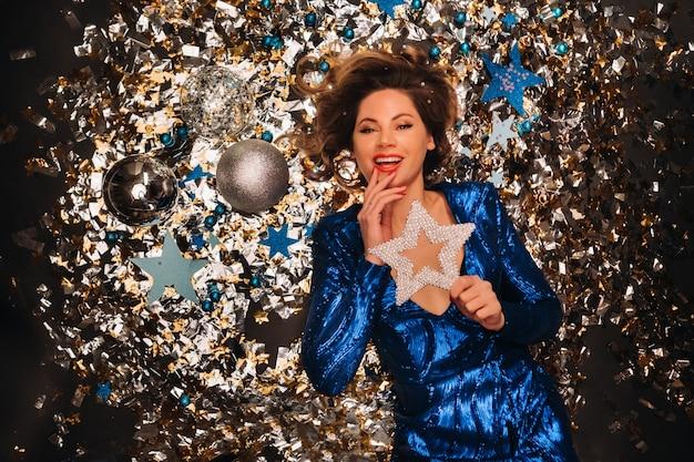 Женщина в синем платье с блестками улыбается и лежит на полу под падающим разноцветным конфетти.