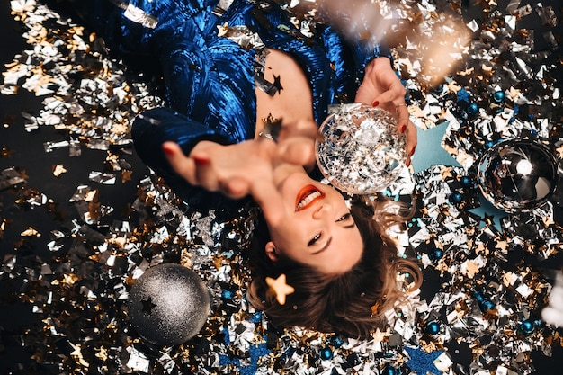 파란색 스팽글 드레스를 입은 여인이 미소 짓고 떨어지는 여러 가지 빛깔의 색종이 아래 바닥에 누워 있습니다.