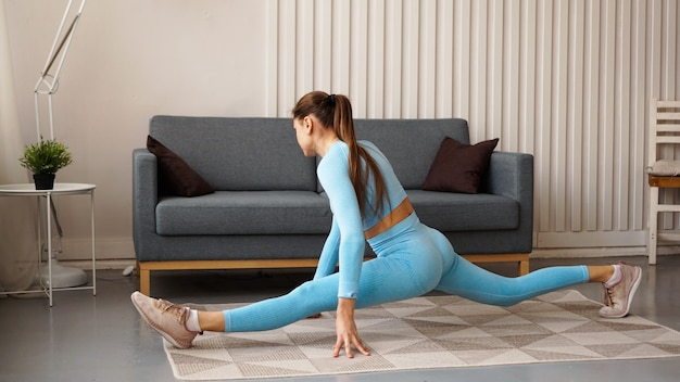 На веревке сидит женщина в синем спортивном костюме. домашние тренировки во время карантина. самостоятельные занятия фитнесом и растяжкой