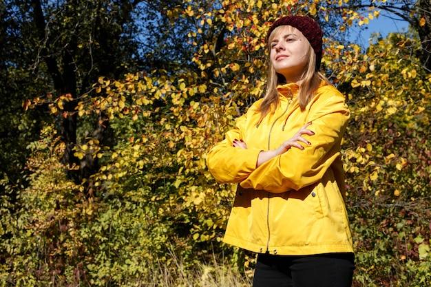 秋の黄色の葉を背景に明るい黄色のレインコートを着た女性。横にテキスト用の空きスペース