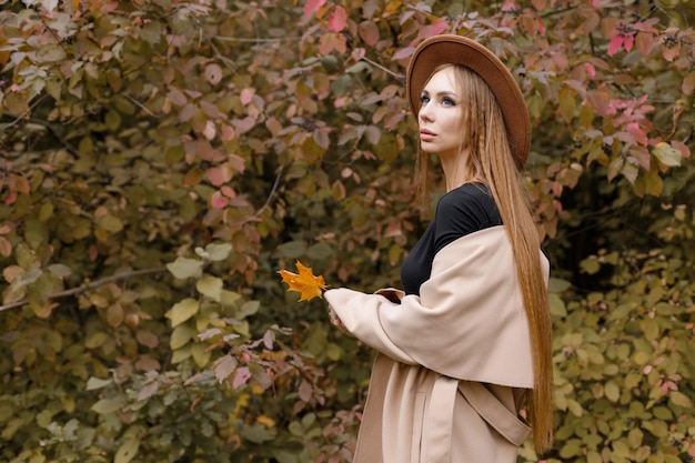 自然の中で秋の背景に茶色の帽子をかぶった女性。閉じる。秋の気分