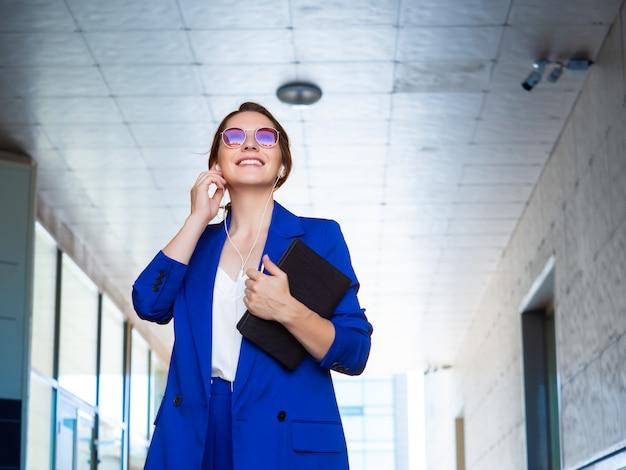 Женщина в деловом костюме несет папку с документами и улыбается, разговаривая по телефону через гарнитуру громкой связи. бизнес-концепция.