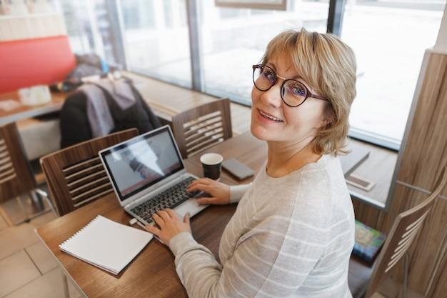 Женщина в кафе работает на ноутбуке. она улыбается. женщина средних лет, взрослая в офисе. удаленная работа.