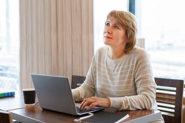 카페에서 노트북 작업을 하는 여성. 비즈니스 및 원격 작업의 개념입니다.