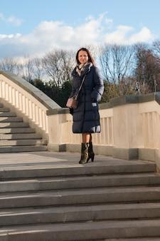 階段の先に立つコートを着た女性