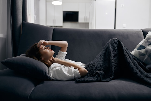 Женщина в уютной комнате лежит на диване, накрытом серым одеялом.