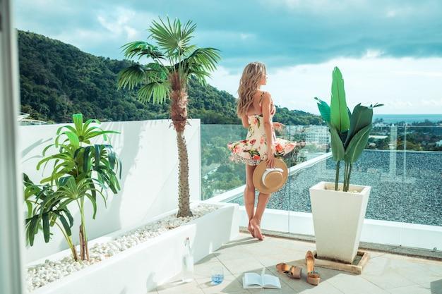 Женщина в платье любуется видом на море и город со своего балкона.