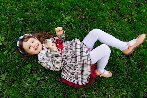 그녀의 머리에 드레스와 화환에있는 여자는 초원과 귀여운 미소에 놓여 있습니다.