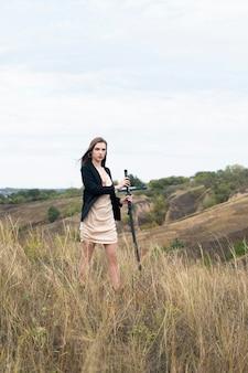 Женщина в платье и куртке гуляет с катаной по холмам