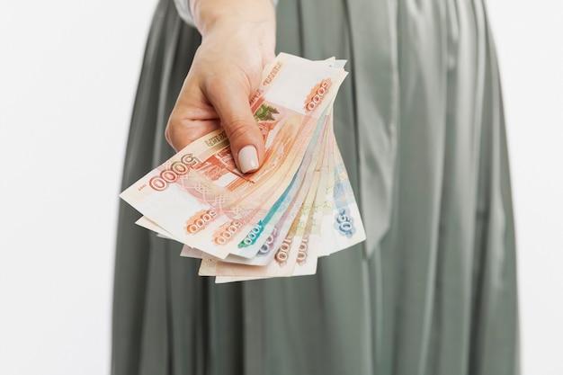 Женщина в платье держит в руке рубли. крупный план.