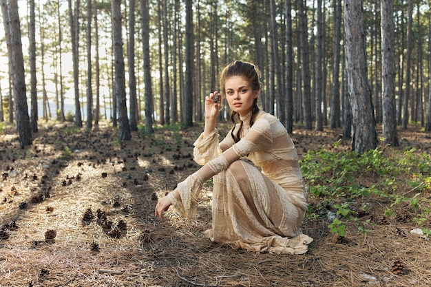 Женщина в платье в лесу на природе и кочки в руке.