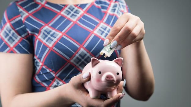 드레스 입은 여자가 돼지 저금통에 달러를 던졌습니다.