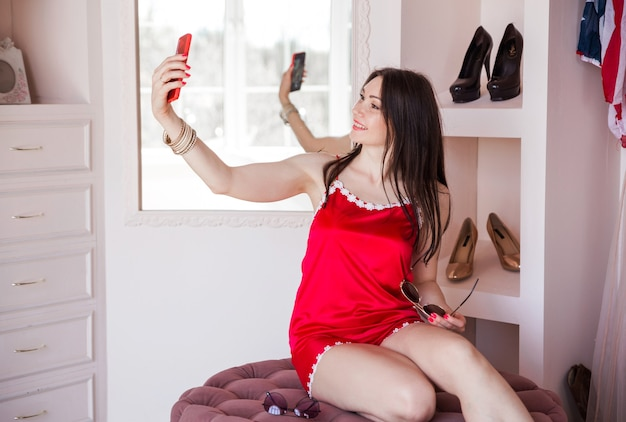 Женщина в раздевалке своей квартиры в красной пижаме держит перед собой телефон и делает селфи.