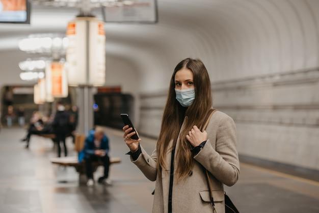코로나 바이러스 확산을 막기 위해 마스크를 쓴 여성이 지하철 역에서 스마트 폰을 들고 포즈를 취하고있다. covid-19에 대한 수술 용 마스크를 쓴 소녀가 지하철 플랫폼에서 기차를 기다리고 있습니다.