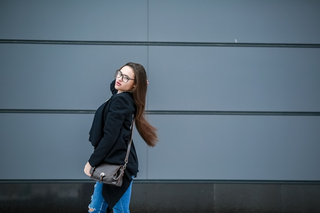 おしゃれなロングコートを着て、眼鏡をかけた女性が通りの灰色の壁を歩く