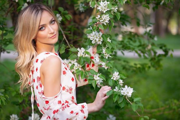 Женщина в цветочном саду в легком белом платье