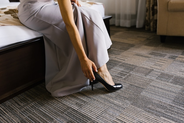 Женщина в сером платье, обувает платье в доме, сидит на кровати