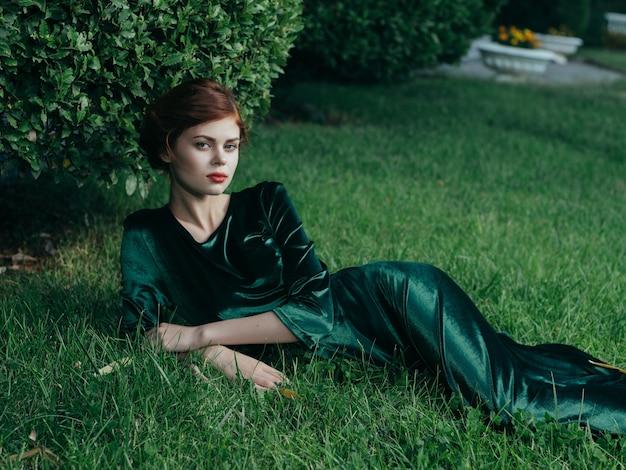 緑のドレスを着た女性が妖精の庭の芝生の上に横たわっています
