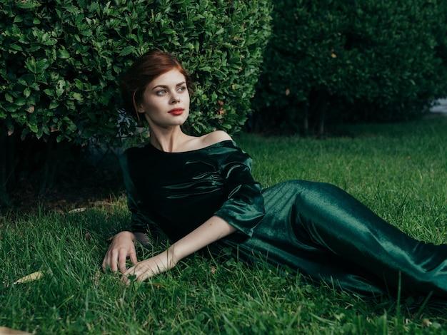 緑のドレスを着た女性が、屋外の贅沢な魅力の芝生の上に横たわっています。高品質の写真
