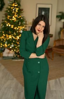 光の花輪とクリスマスツリーの背景に緑のドレスを着た女性