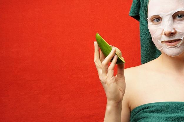Женщина в зеленом полотенце, с косметической маской на лице, держит в руке авокадо. знамя