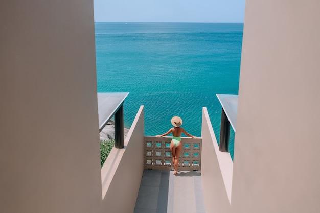 ホテルのテラスに立っている帽子をかぶった女性が海の地平線を眺める