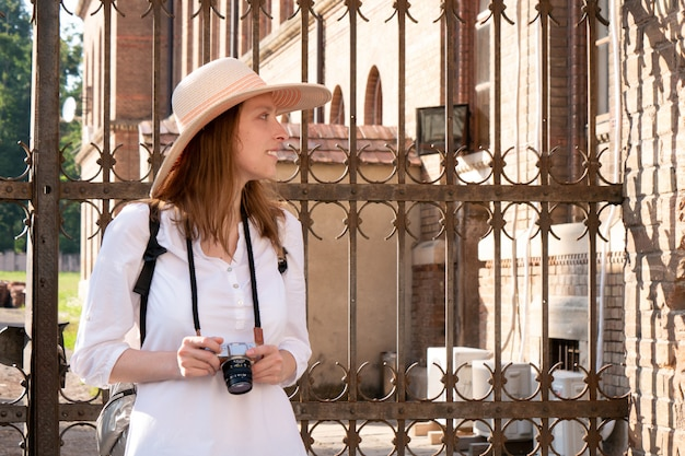 모자를 쓴 여인과 배낭이 달린 흰색 운동복이 여행하고 사진을 찍습니다.
