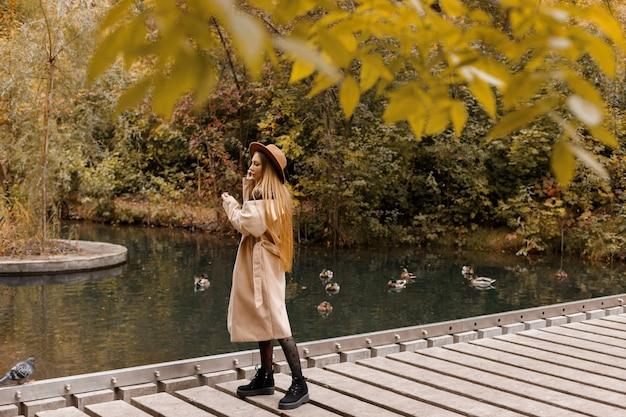秋の公園で帽子と秋の服を着た女性。テキスト用の空き容量