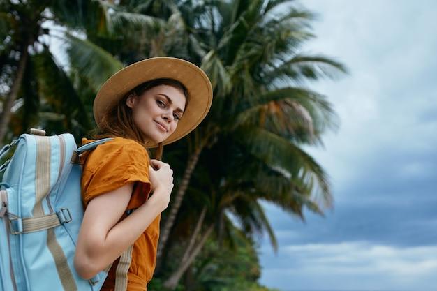 帽子とバックパックを持つ女性が島の自然のカメラで笑顔